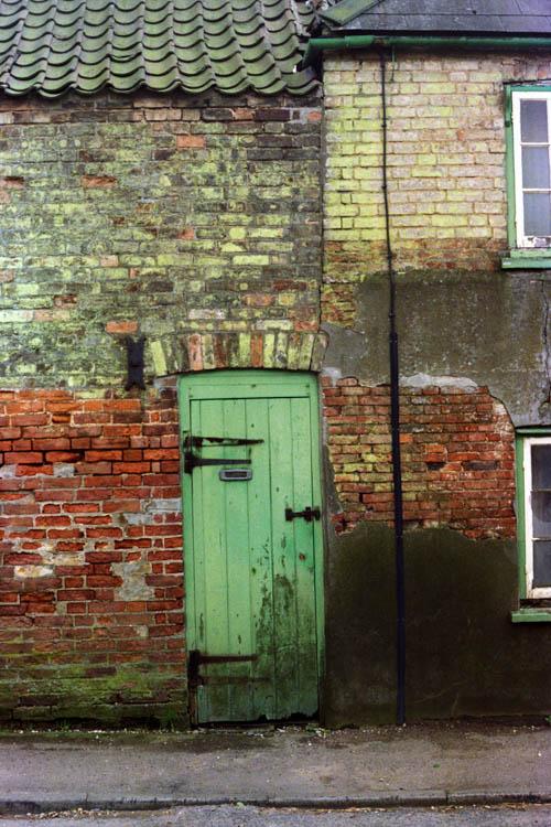 green_door_brick_wall_wrk